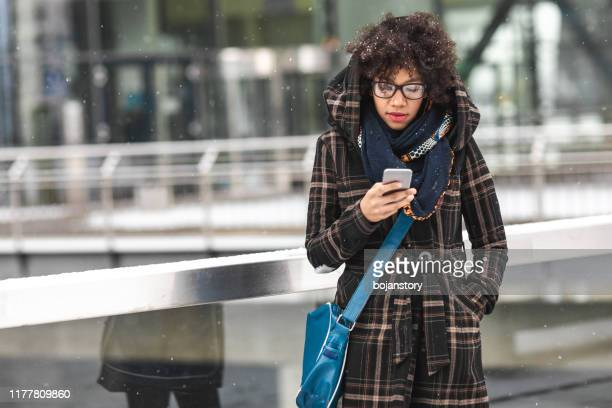 beautiful young woman using smart phone outdoors - coat stock pictures, royalty-free photos & images