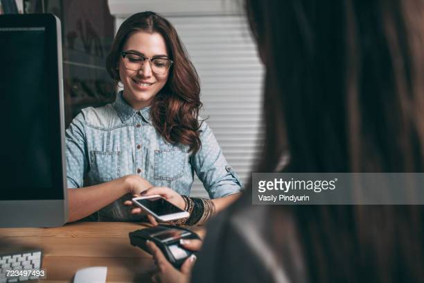 Beautiful young woman using smart phone to pay at counter