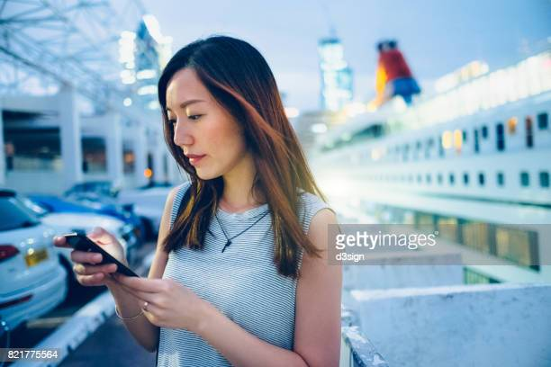 Beautiful young woman using smartphone and waiting to get onboard in cruise terminal