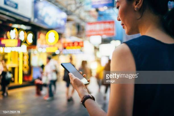 beautiful young woman using smartphone in busy city street, against colourful neon commercial sign and city buildings - prosperity stock pictures, royalty-free photos & images