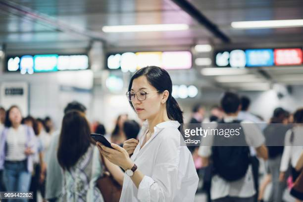 beautiful young woman using smartphone in subway station during rush hour - human settlement stock pictures, royalty-free photos & images