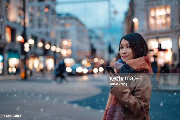 beautiful young woman using smartphone on the high street - solo adulti foto e immagini stock