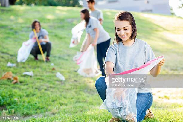 Beautiful young woman volunteering to clean up the park