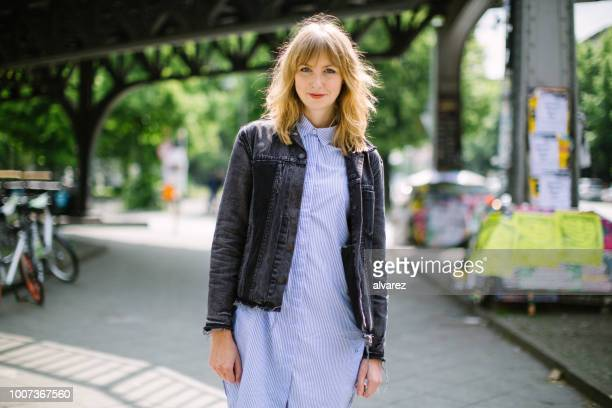 beautiful young woman walking along city street - fashionable stock pictures, royalty-free photos & images