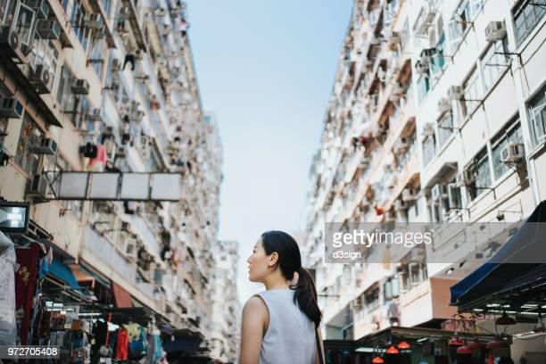 Beautiful young woman walking along local city market looking up to sky in Hong Kong
