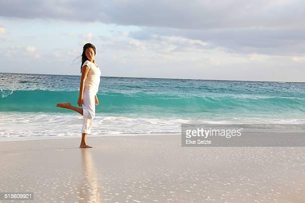 Beautiful young woman walking at seashore