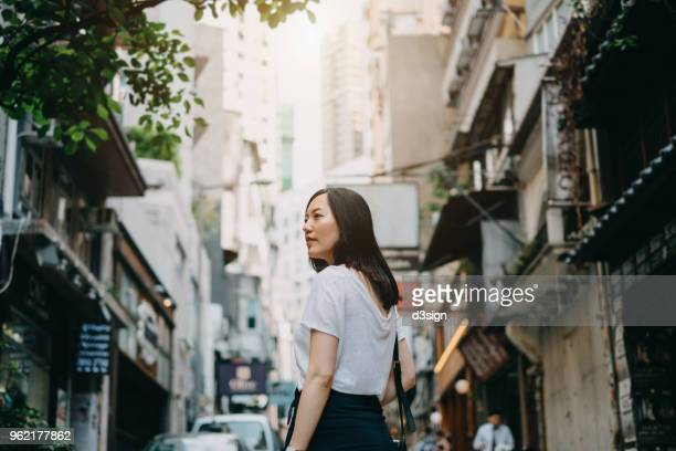 beautiful young woman walking down streets of hong kong - central stock pictures, royalty-free photos & images