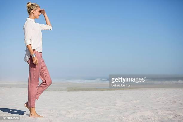 Beautiful young woman walking on sunny beach