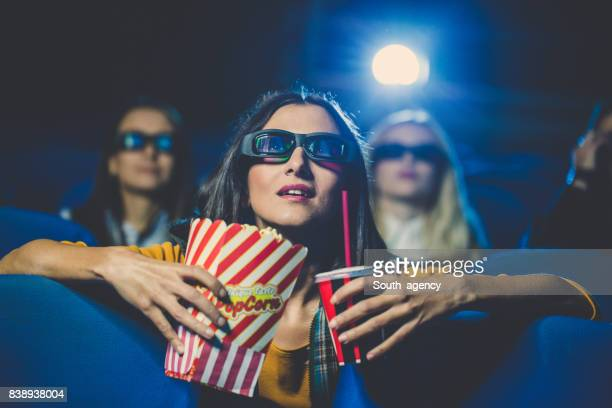 Beautiful young woman watching movie in theater