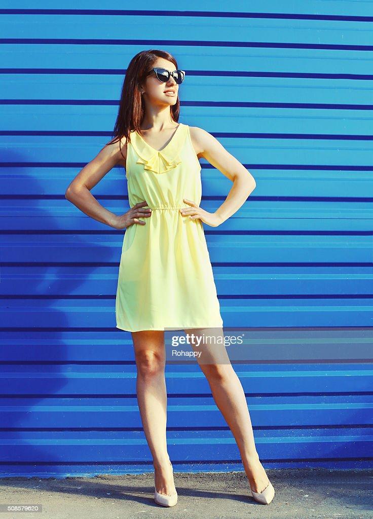 Bellissima giovane donna che indossa occhiali da sole e un vestito giallo : Foto stock