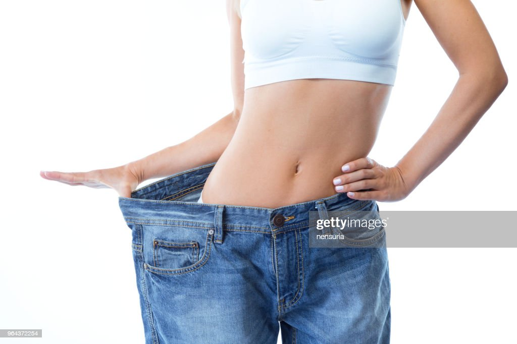 Beautiful young woman wearing big jeans over white background. : Stock Photo
