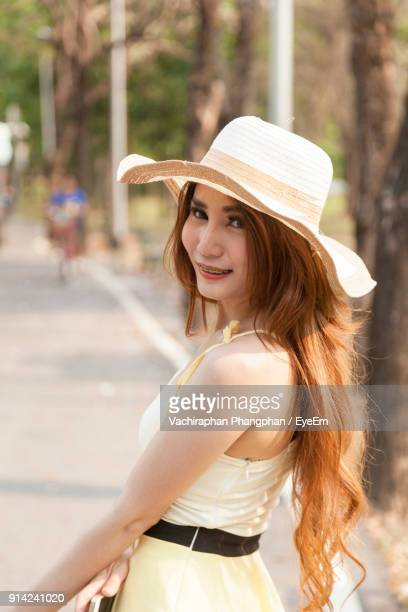 Beautiful Young Woman Wearing Hat Standing At Park