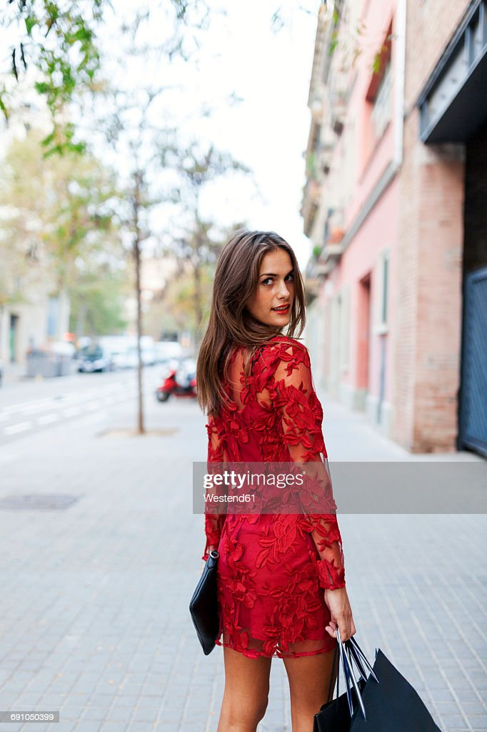 Beautiful young woman wearing red dress carrying shopping bags : Stock-Foto
