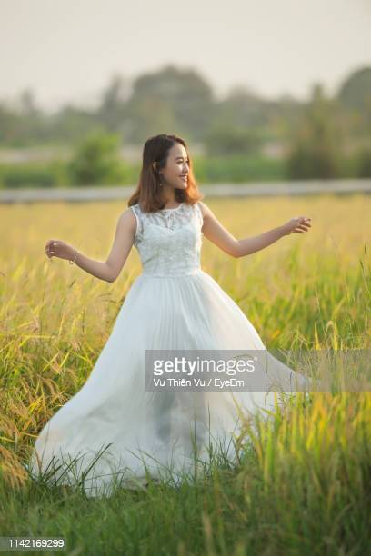 beautiful young woman wearing white dress while standing by plants on land - 白のドレス ストックフォトと画像