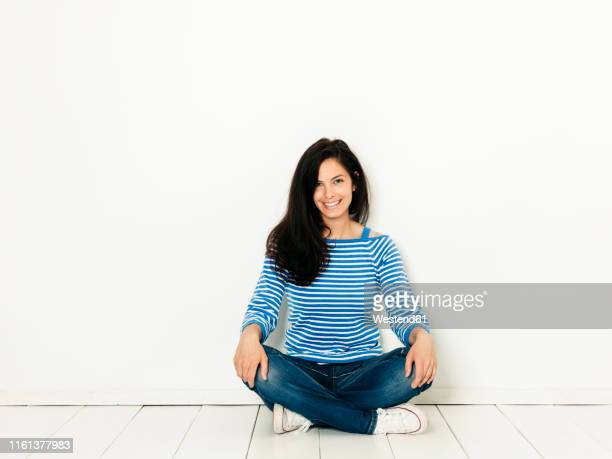 beautiful young woman with black hair and blue white striped sweater sitting on the ground in front of white background - piernas cruzadas fotografías e imágenes de stock