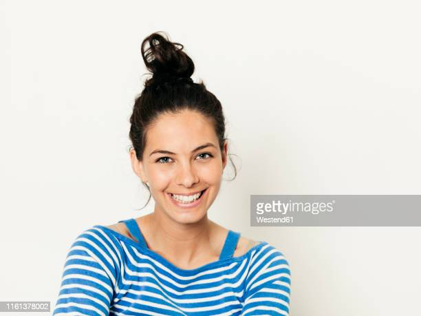 beautiful young woman with black hair and blue white striped sweater is posing in front of white background - おだんごヘア ストックフォトと画像