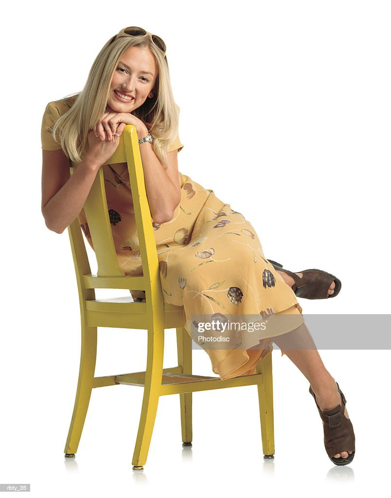 beautiful young woman with blonde hair wearing a yellow sundress gold sunglasses and sandals sits sideways on a yellow wooden chair with her arms resting on the back and smiles at the camera : Foto de stock