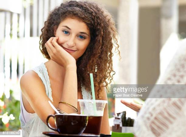 beautiful young woman with blue eyes and curly hair sitting at a cafe with chin in her hands smiling at camera