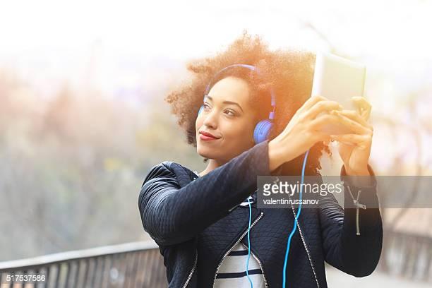 Belle jeune femme avec un casque à l'aide de tablette numérique bleu