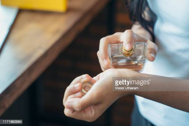 beautiful young woman with bottle of perfume at home. - perfume stock pictures, royalty-free photos & images