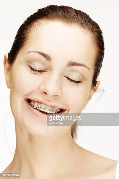 Bellissima giovane donna sorridente con bretelle su sfondo bianco