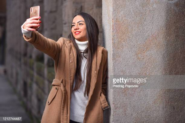 beautiful young woman with brown coat taking selfie while leaning over street wall with space for text - kumanovo stock pictures, royalty-free photos & images