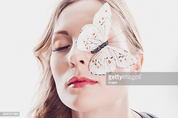 Beautiful young woman with butterfly on her face