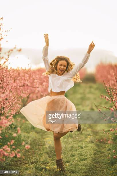 beautiful young woman with cherry blossom at spring - springtime stock pictures, royalty-free photos & images