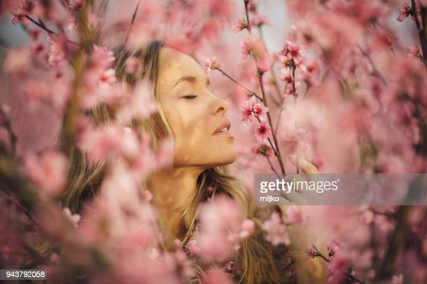 beautiful young woman with cherry blossom at spring - peach flower stock pictures, royalty-free photos & images