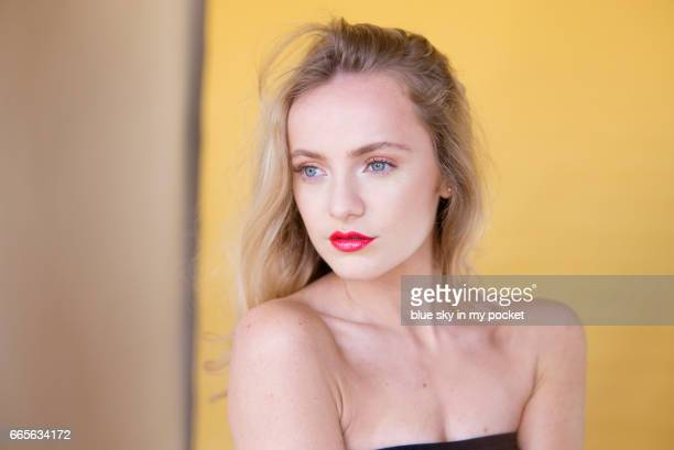A beautiful young woman with clear sharp skin and flawless movie star make-up with red glossy lips.