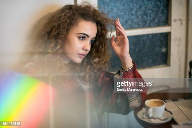 Beautiful young woman with curly hair drinking coffee at home