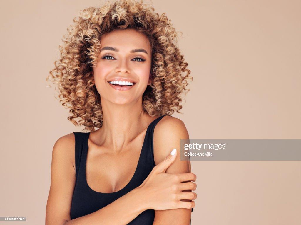 Bella giovane donna con i capelli ricci : Foto stock