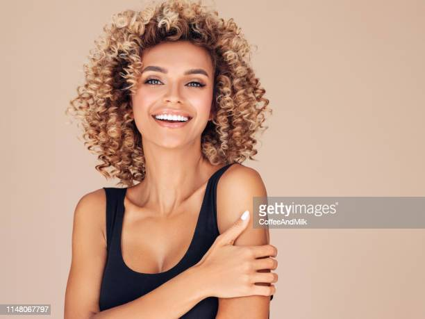 beautiful young woman with curly hair - beauty stock pictures, royalty-free photos & images