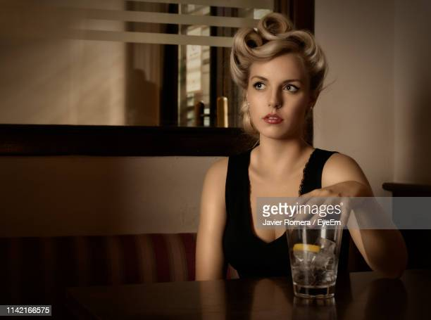beautiful young woman with drink sitting at restaurant table - mulher fatal imagens e fotografias de stock