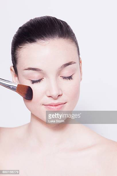 Beautiful young woman with eyes closed applying blusher