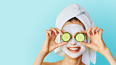 Beautiful young woman with facial mask on her face holding slices of cucumber