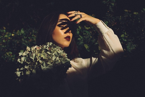 Beautiful Young Woman With Fingers Shadow On Face In Park At Night - gettyimageskorea