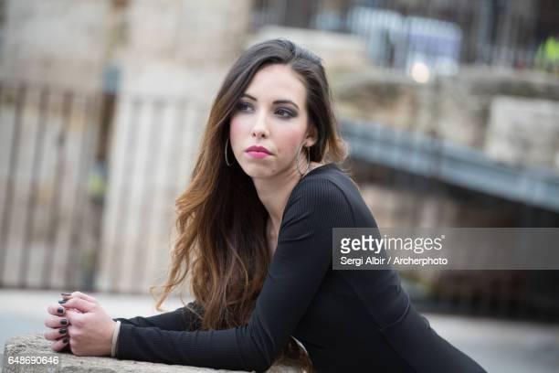 Beautiful young woman with great long brown hair in an urban garden