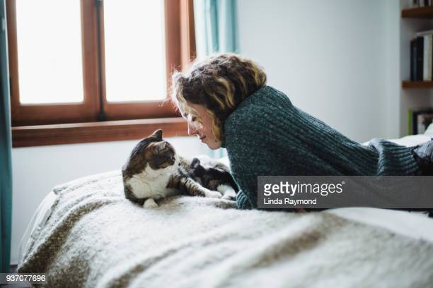 beautiful young woman with her cat on a bed - cat family stock pictures, royalty-free photos & images