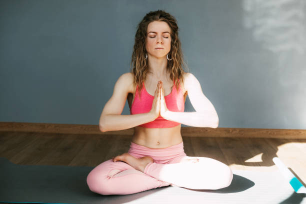 A Beautiful Young Woman With Her Eyes Closed Meditates In The Lotus Position In The Classroom.