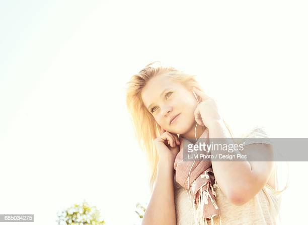 Beautiful young woman with long blond hair listening to music outdoors on her smart phone in a city park in autumn