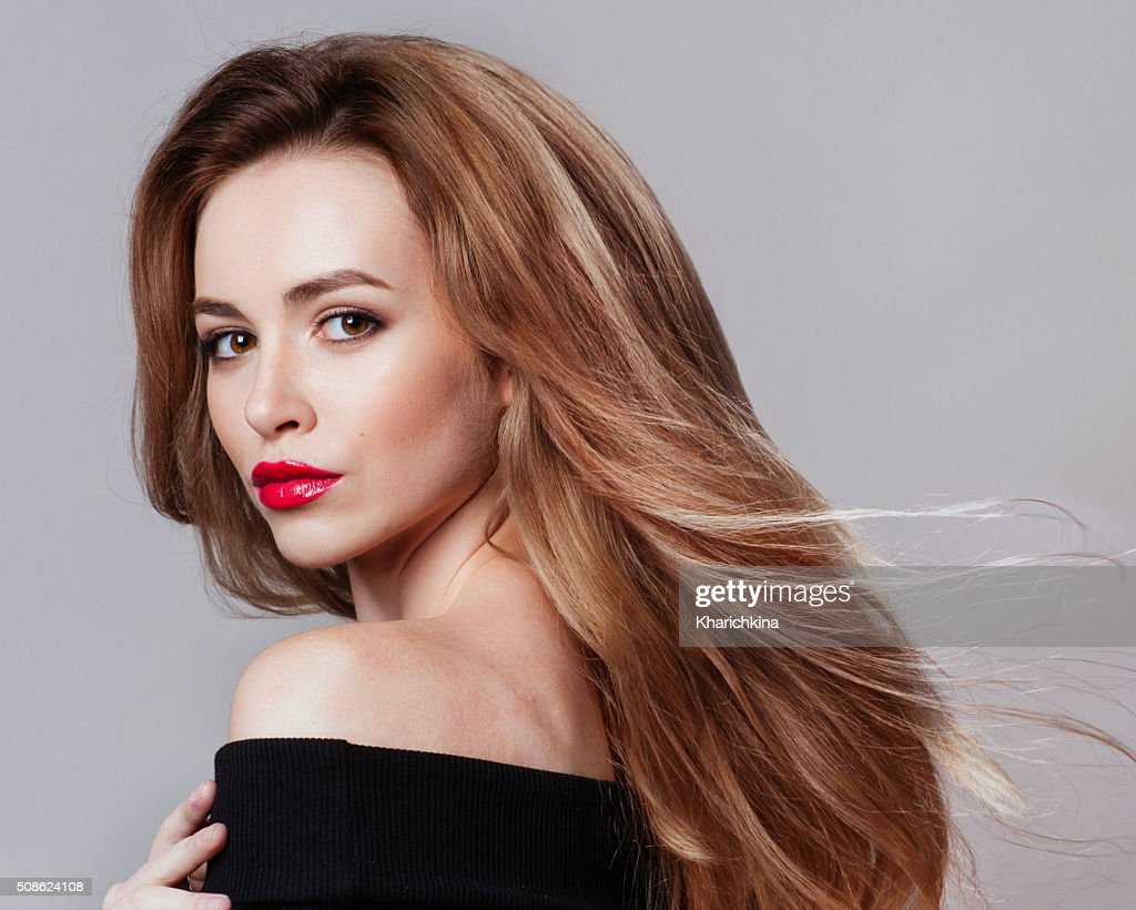 Beautiful young woman with long hair and jewelery : Stock Photo