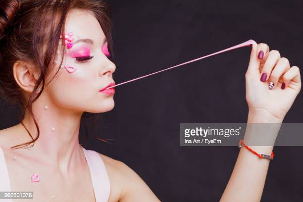 Beautiful Young Woman With Make-Up Stretching Bubble Gum Against Gray Background