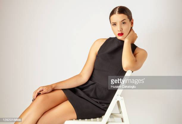 beautiful young woman with mini black dress sitting on white chair front of white background. - mini dress stock pictures, royalty-free photos & images
