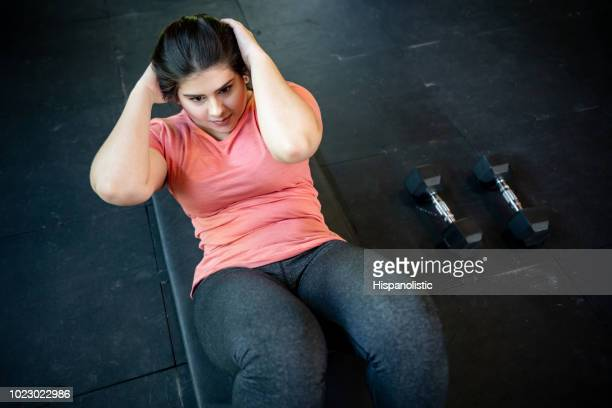 beautiful young woman with overweight doing abs at the gym - effort stock pictures, royalty-free photos & images