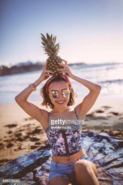Beautiful young woman with pineapple at the beach