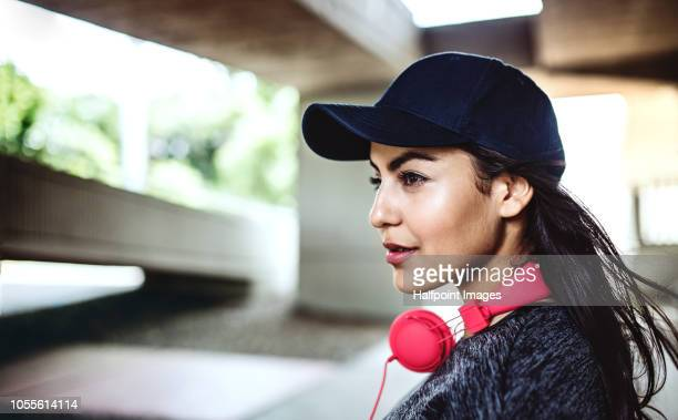 A beautiful young woman with red headphones under the bridge in the city. Copy space.