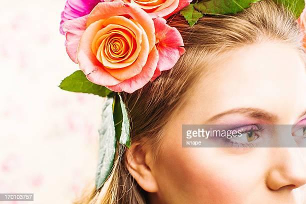 Belle jeune femme avec des roses dans les cheveux