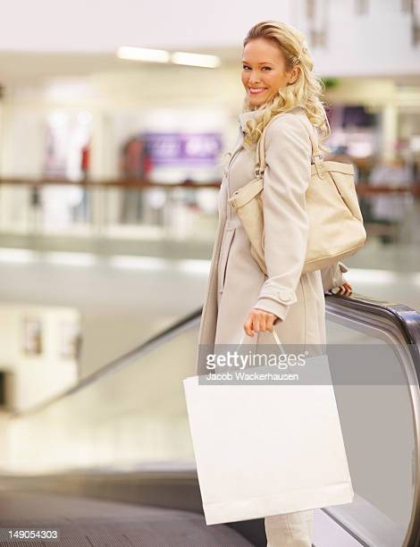 Beautiful young woman with shopping bags standing by escalator