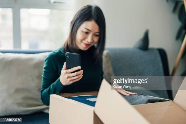 beautiful young woman with smart phone unwrapping package at home - unboxing stock pictures, royalty-free photos & images